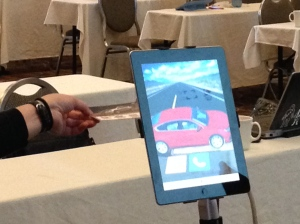Design Mill demonstrates how they take a car dealership post card and use an iPad to overlay show the overlaid 3D model of the car.